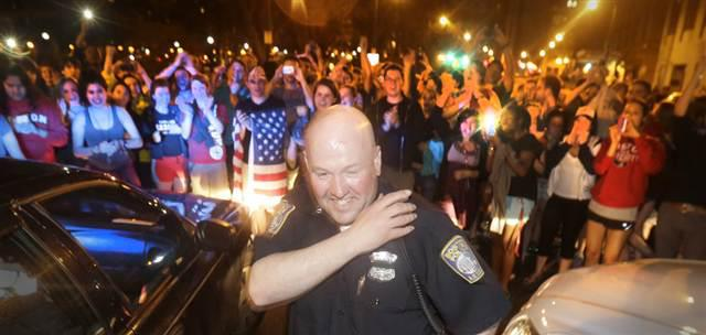 A police officer reacts to the arrest of Dzhokhar Tsarnaev in Watertown, Mass. (Julio Cortez-AP)